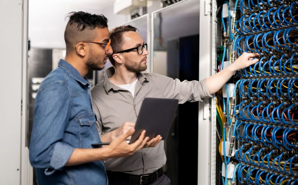 Serious thoughtful young multi-ethnic computer support specialists in casual clothing standing at server racks and using laptop while analyzing network problem