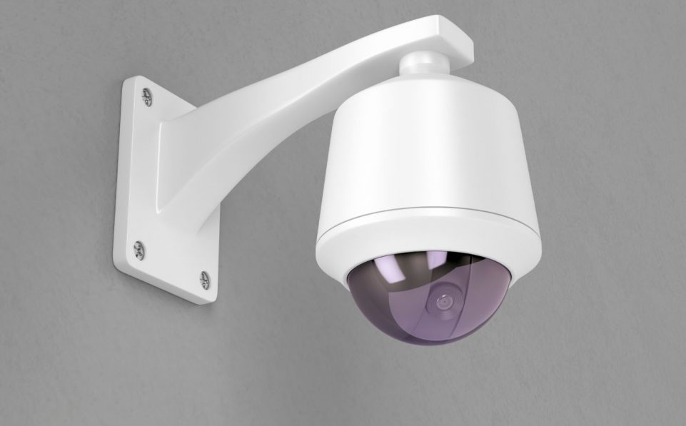 Surveillance camera attached on grey wall